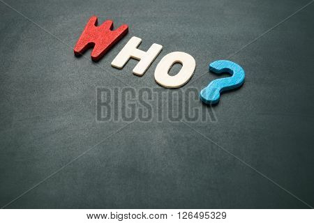 Text 'who' wording on blackboard - concept of 5 Ws questions - colorful alphabet made from wood