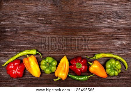 Different kinds of pepper on dark wooden background top view