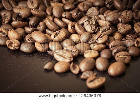 Coffee beans on a wooden table close up