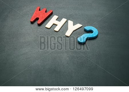 Text 'why' wording on blackboard - concept of 5 Ws questions - colorful alphabet made from wood