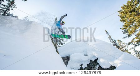 Flying snowboarder in the mountains making a trick.