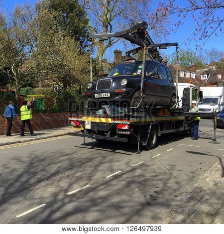 LONDON - APRIL 20: A London Black Cab is impounded by Traffic Wardens for a parking violation on Frognal Lane on April 20, 2016 in Hampstead, London, UK.