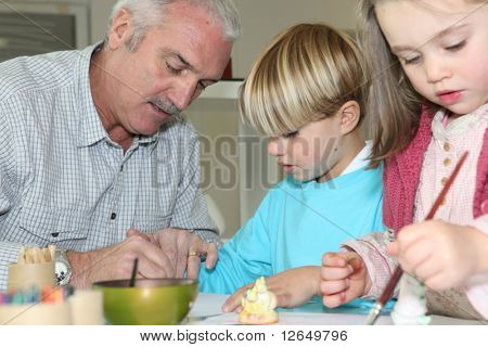 Senior man making watercolors with children