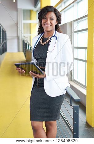 Friendly and attractive of a african american woman practitioner standing in a glass hall office of the clinic and examining documents