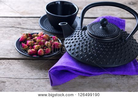 Dry rose tea in bowl and traditional asian tea set on aged wooden background. Selective focus is on tea. Toned image.