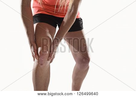 young sport woman with strong athletic legs holding knee with his hands in pain after suffering ligament injury during a running workout training isolated white background