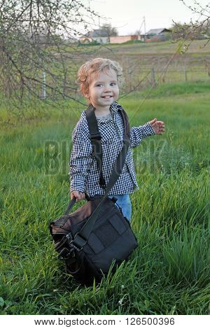 Little boy stands with a bag from the camera on the background of autumn nature. assistant photographer working in the open air.