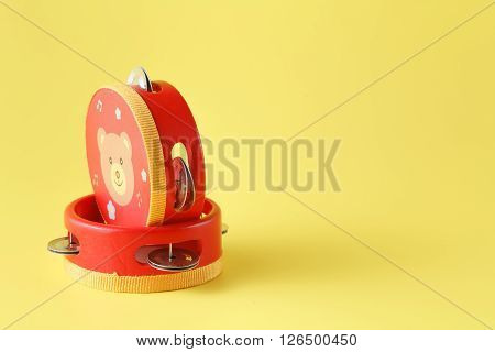 Two red Kids tambourine on yellow with copy space