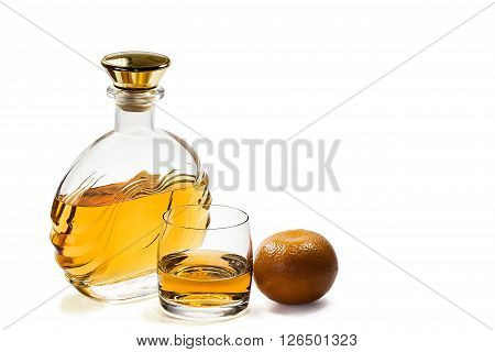 Bottle and a glass of whiskey with a Mandarin on a white background