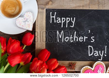 Valentines day coffee with red tulips bouquet, happy mothers day on blackboard