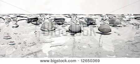 glass pebble stone on wet water surface with multiple drops