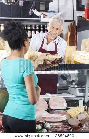 Senior Salesman Giving Cheese To Female Customer