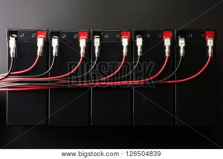 Rechargeable batteries, and electrical wires. Industrial battery hooked up in parallel with long red and black cable bundles, coming from the terminal.