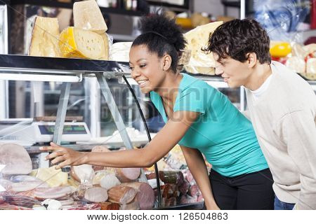 Multiethnic Couple Choosing Product From Display Cabinet