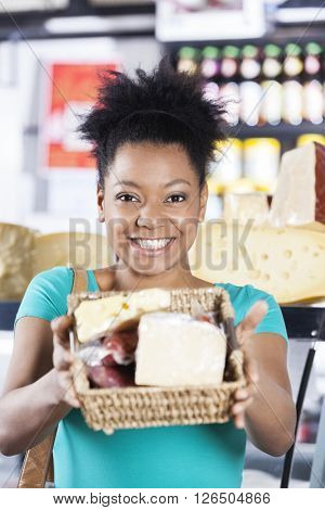 Happy Woman Showing Cheese Basket In Grocery Store