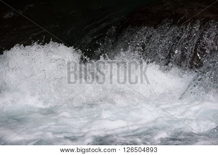Rapid water splashes of an white water river or stream.