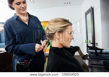 Beautiful Hairdresser Braiding Client's Hair