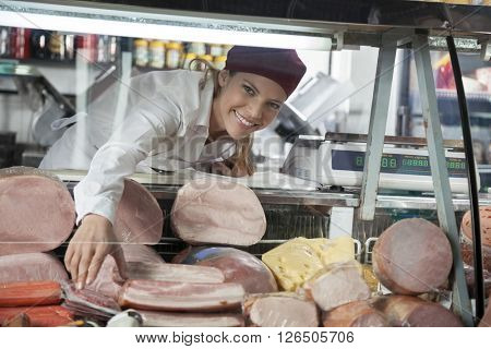 Saleswoman Arranging Products In Display Cabinet At Grocery Stor
