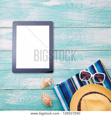 Blank empty tablet computer on beach. Trendy summer accessories on wooden background pool. Flip-flops on beach. Tropical flower orchid. Flat mock up for design. Top view.