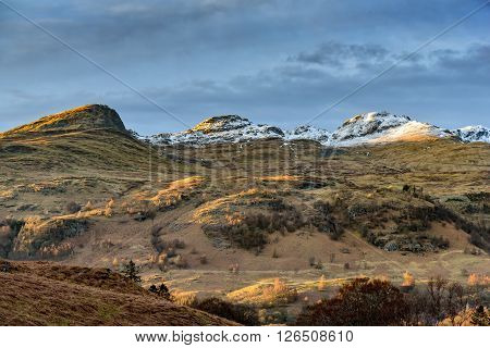 Snow covered summits of the Tarmachan Ridge in evening light in Perthshire.