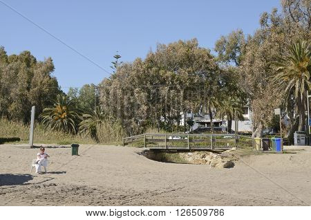 MARBELLA, SPAIN - APRIL 9, 2016: Woman dressed in white sitting on a chair next to a little wooden bridge in the beach of Marbella Spain.
