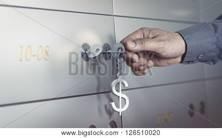 Safe deposit in a bank vault hand about to turn a key to open a safe box. Financial concept
