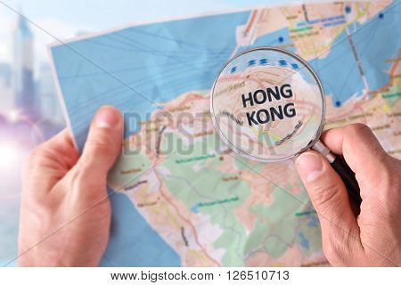 Man Consulting A Map Of Hong Kong With Magnifying Glass