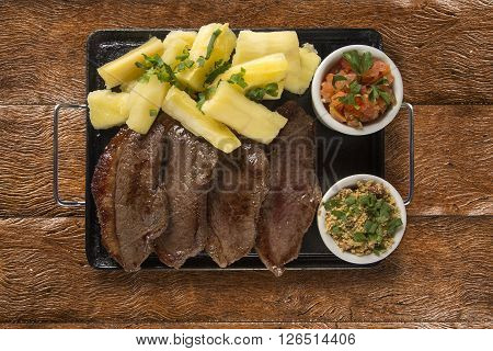 picanha portion and manioc fries. Wood background.
