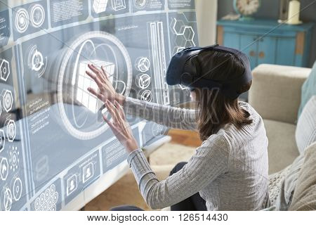 Woman Sits On Sofa At Home Wearing Virtual Reality Headset