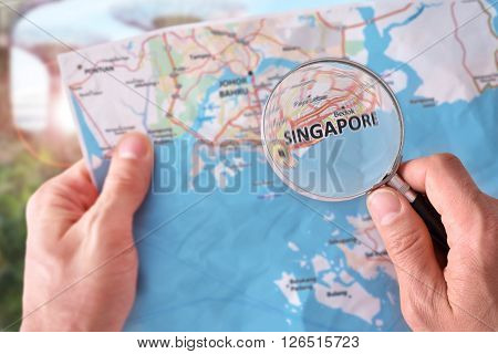 Man Consulting A Map Of Singapore With A Magnifying Glass