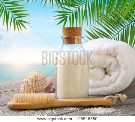 Fluffy towels with sea salt and seashells on beach table