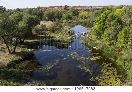 the small still hush river and trees on the banks