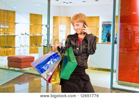 "a girl with shopping bags in a mall is talking on a cell phone  - See similar images of this ""Gorgeous shopping women"" series in my portfolio"