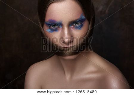 Beauty Model with blue Makeup on Eyes and creative Hairstyle looking at Camera