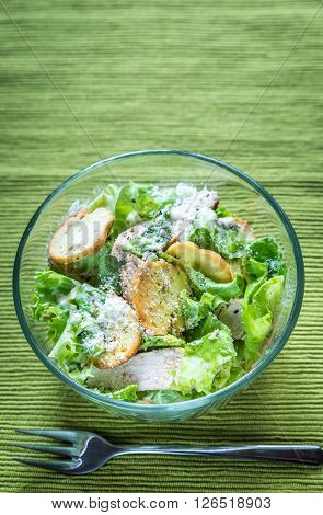 Glass bowl of chicken Caesar salad: top view