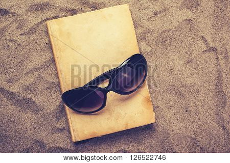 Reading favourite old book on summer vacation beach holiday top view of a book and sunglasses in warm beach snow.