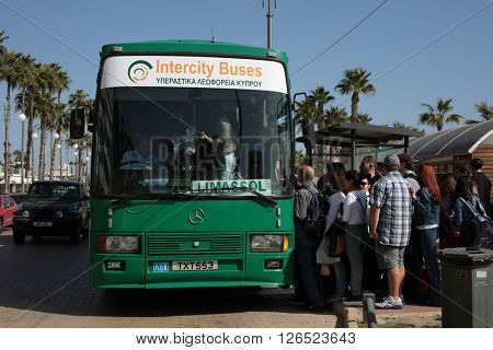 LARNACA, CYPRUS - MARCH 13, 2016: Lot of people in front of the intercity bus want to reach Limasol in the last day of the traditional carnival. The festival is a 10 day colorful annual event