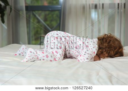 Smiling toddler girl playing in a night clothes on the bed in the bedroom with white linens. Happy curled red-haired baby. Girl hides her face.