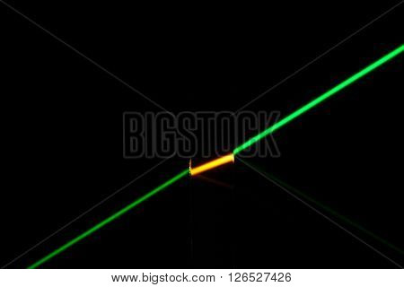 A green laser penetrating a dark colored glass.