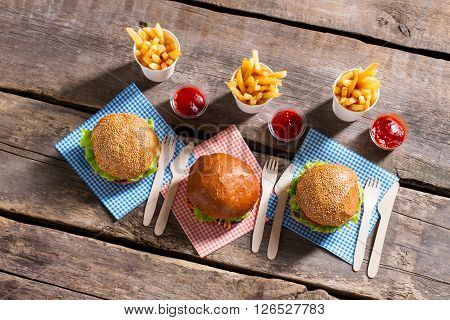 Burgers with cutlery and fries. Hamburgers and cutlery on table. Freshly cooked meal at bistro. Dinner in fast food cafe.