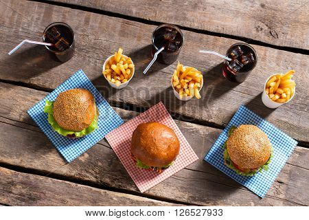 Burgers with fries and cola. Hamburgers with cola on table. Cool drinks and tasty burgers. Fresh vacation meal in diner.