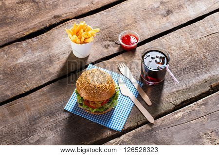 Burger with ketchup and cola. Burger menu on wooden table. Junk food and cool drink. High-calorie lunch in bistro.