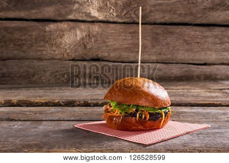 Tasty burger on stick. Old table with delicious hamburger. Grilled beef and fresh buns. Try the taste of energy.