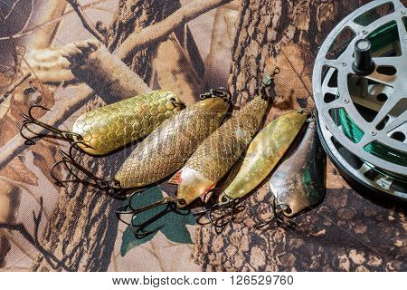 inertia fishing reel with oscillating old USSR lures on the camouflage