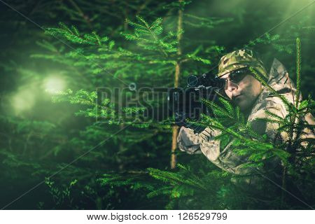 Hunting Poacher in Dense Pine Forest. Hunter in Camouflage with Hunting Rifle.
