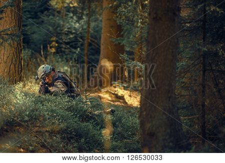 Military Operation in Forest. Soldier with Assault Rifle Laying Covered and Spotting Enemy. Military Concept.