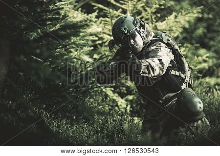 Special Forces Soldier. Camouflaged Marine Soldier Shooting Assault Rifle. Army Military Mission Concept Photo.