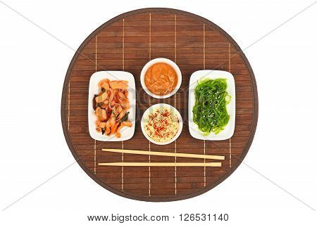 Two portions of seafood marinated salad with octopus cuttlefish and seaweeds in with chopsticks and sauce on dark round bamboo mat top view
