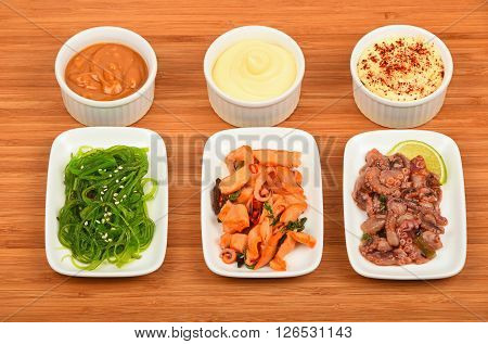 Three portions of seafood marinated salad with octopus cuttlefish squid and seaweeds in white plates with sauce on wooden table high angle view