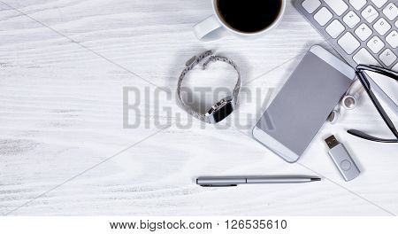 Overhead view of desktop work items consisting of computer keyboard cell phone ear phone coffee watch thumb drive reading glasses and pen.